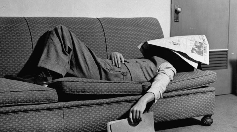 Personne allongée, le visage caché sous un journal